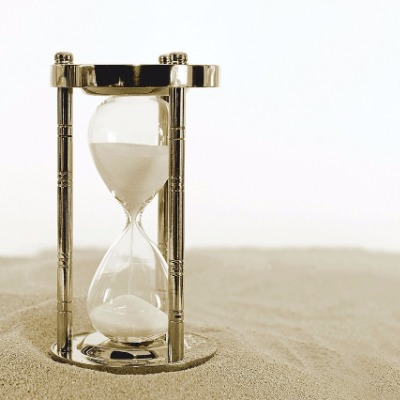 An hourglass with sand running.