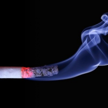 lit cigarette with smoke on black background