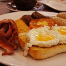 English breakfast with sausage, bacon, eggs and toast