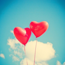 red heart-shaped balloons in the sky