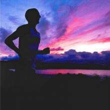 man running past purple sky and water