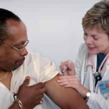 female doctor giving a vaccination to adult male